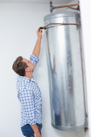 Side view of a technician servicing an hot water heater photo