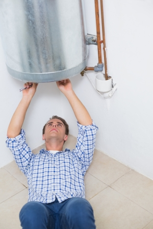 Concentrated young technician servicing an hot water heater photo