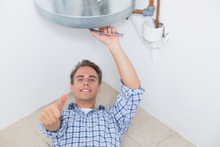 Portrait of a smiling technician gesturing thumbs up by hot water heater photo