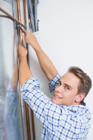 Side view portrait of a young technician servicing an hot water heater pipes photo