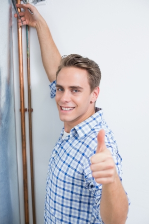 Young technician servicing an hot water heater pipes while gesturing thumbs up photo