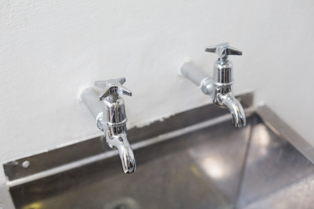 stainless steel kitchen: Close up of two taps and stainless steel kitchen sink