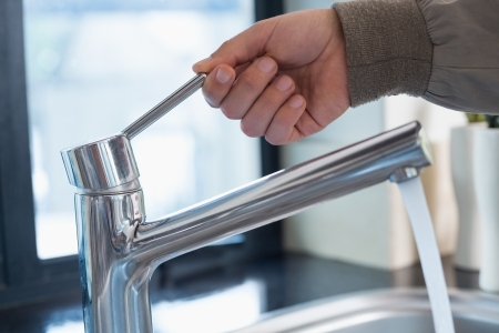 llave agua: Detalle de primer plano de una mano los fontaneros de abrir un grifo de agua en el cuarto de ba�o Foto de archivo