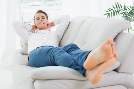 Full length of a relaxed young man lying on sofa in a bright house photo