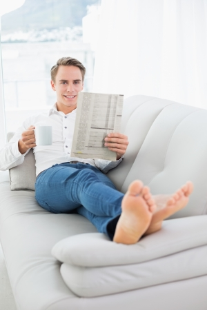 Relaxed man with coffee cup while reading newspaper on sofa in a bright house photo