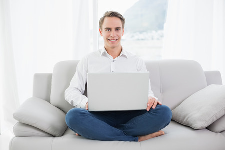 Portrait of a smiling casual young man using laptop on sofa in a bright house photo