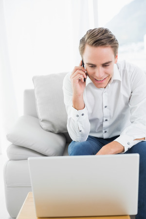 Casual young man using cellphone and laptop on sofa in a bright house photo