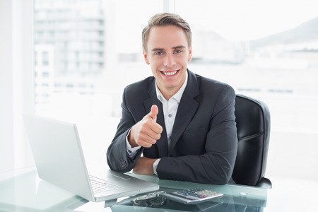 Portrait of a smiling young businessman with laptop gesturing thumbs up at office desk