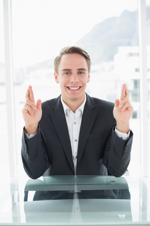 Portrait of a smiling young businessman with fingers crossed sitting at office desk photo