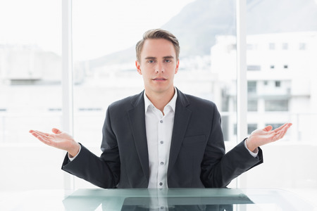Portrait of a serious young businessman with hand gesture sitting at office desk photo