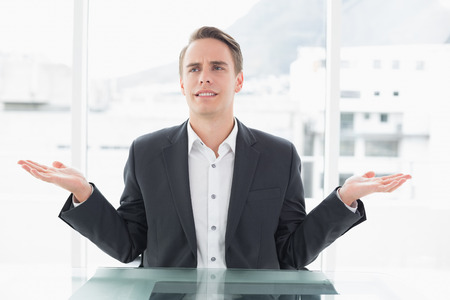 displeased businessman: Displeased young businessman with hand gesture sitting at office desk