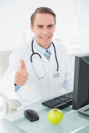 Portrait of a smiling male doctor using computer while gesturing thumbs up at medical office photo