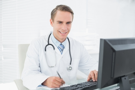 Portrait of a smiling male doctor writing a note while using computer at medical office photo