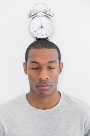 Close up of a man with an alarm clock on top of his head over white background Stock Photo