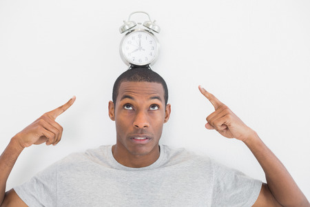 Close up of a man pointing at alarm clock over his head against white background photo