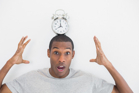 late thirties: Close up of a shocked man with an alarm clock on top of his head over white background Stock Photo
