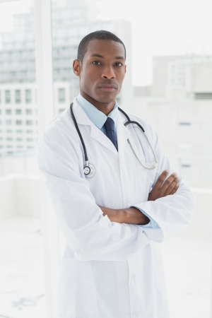 Portrait of a serious male doctor standing with arms crossed in a medical office