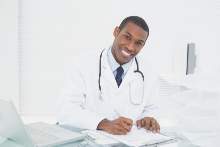 Portrait of a smiling male doctor writing a note at medical office photo