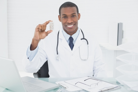 Portrait of a smiling male doctor holding a prescription bottle in medical office photo