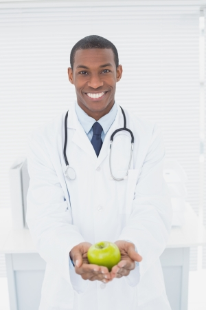 Portrait of a smiling male doctor holding a green apple at medical office photo