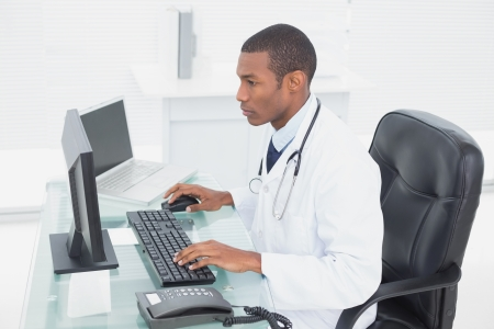 Side view of a concentrated male doctor using computer at medical office Reklamní fotografie