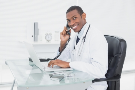 Side view portrait of a smiling male doctor using phone and laptop at medical office