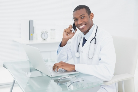 Portrait of a smiling male doctor using cellphone and laptop at medical office photo