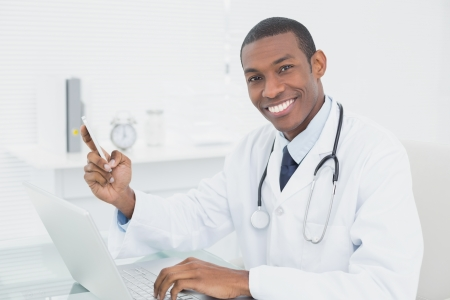 Portrait of a smiling male doctor text messaging while using laptop at medical office