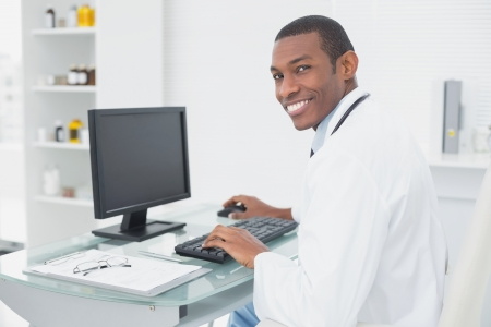 Side view of a smiling male doctor using computer at medical office photo