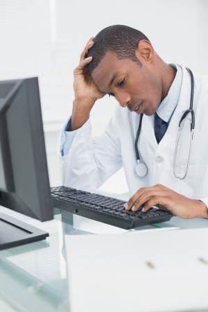 Worried male doctor using computer at medical office photo