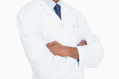 Close up mid section of a male doctor with arms crossed against white background photo