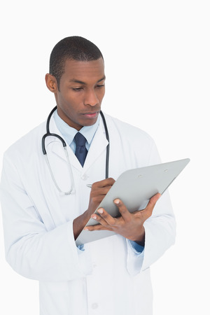 Serious male doctor writing on clipboard against white background photo