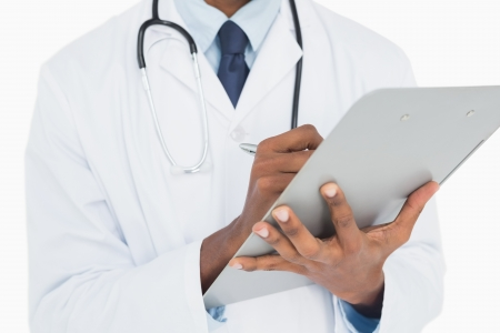 Close up mid section of a male doctor writing on clipboard against white background photo
