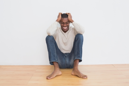 Full length of an angry casual Afro young man sitting on floor against wall