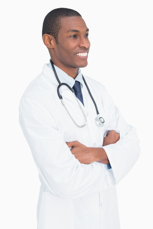 Smiling male doctor standing with arms crossed against white background photo