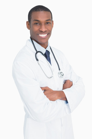 Portrait of a smiling male doctor with arms crossed against white background photo