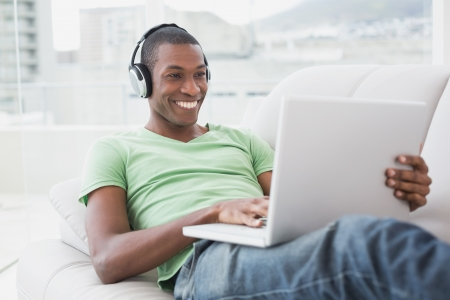 Relaxed smiling young Afro man with headphones using laptop on sofa in a bright house photo