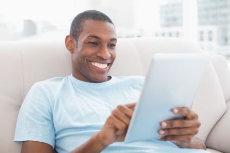 afro man: Casual smiling young Afro man using digital tablet on sofa in a bright house