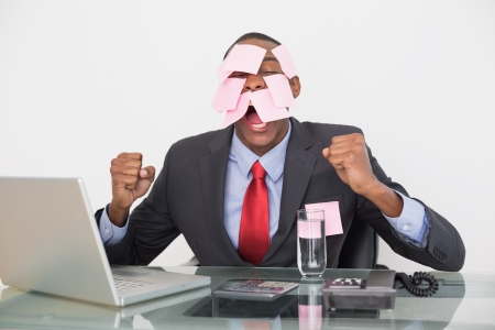 Frustrated Afro businessman with blank notes on face and laptop over white background