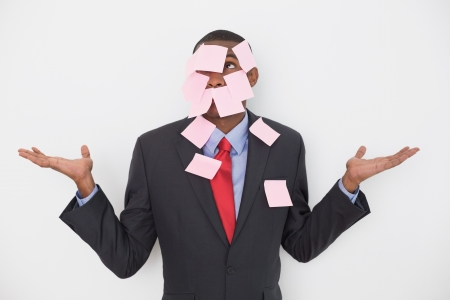 Young Afro businessman covered in blank notes over white background photo