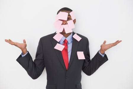 Portrait of an Afro businessman covered in blank notes over white background photo