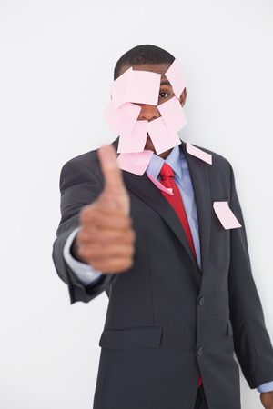 Portrait of an Afro businessman covered in blank notes gesturing thumbs up over white background photo