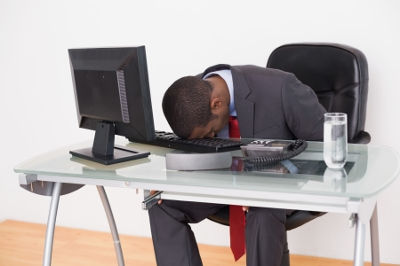 Young Afro businessman resting head on keyboard in the office photo
