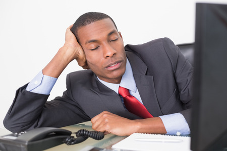 Young Afro businessman resting at desk against white background photo