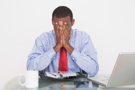 Frustrated young Afro businessman with hands covering face at desk against white background photo