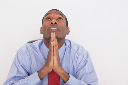 joined hands: Primer plano de un hombre de negocios serio afro joven mirando hacia arriba con las manos juntas contra el fondo blanco Foto de archivo