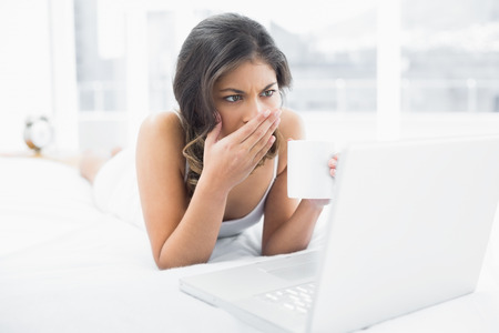 Shocked casual young woman drinking coffee while using laptop in bed at home photo