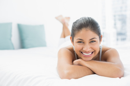 woman relaxing: Portrait of a pretty young woman lying in bed at home Stock Photo