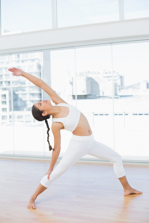 Full length of a fit young woman stretching hand in fitness studio Reklamní fotografie