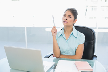 Thoughtful businesswoman looking up while using laptop on desk in a bright office photo